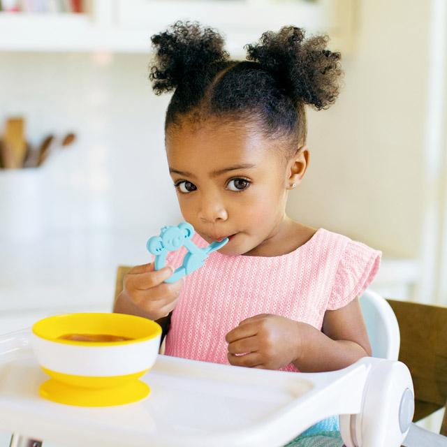 Young girl uses the Blue Koala Baby Toon™ Silicone Teether Spoon.