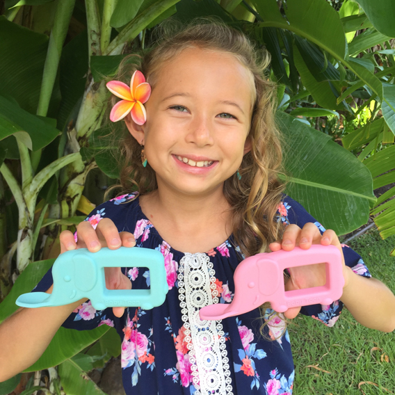 The Baby Toon™ Silicone Teether Spoon creator Cassidy holding a blue and pink elephant baby toon spoons.