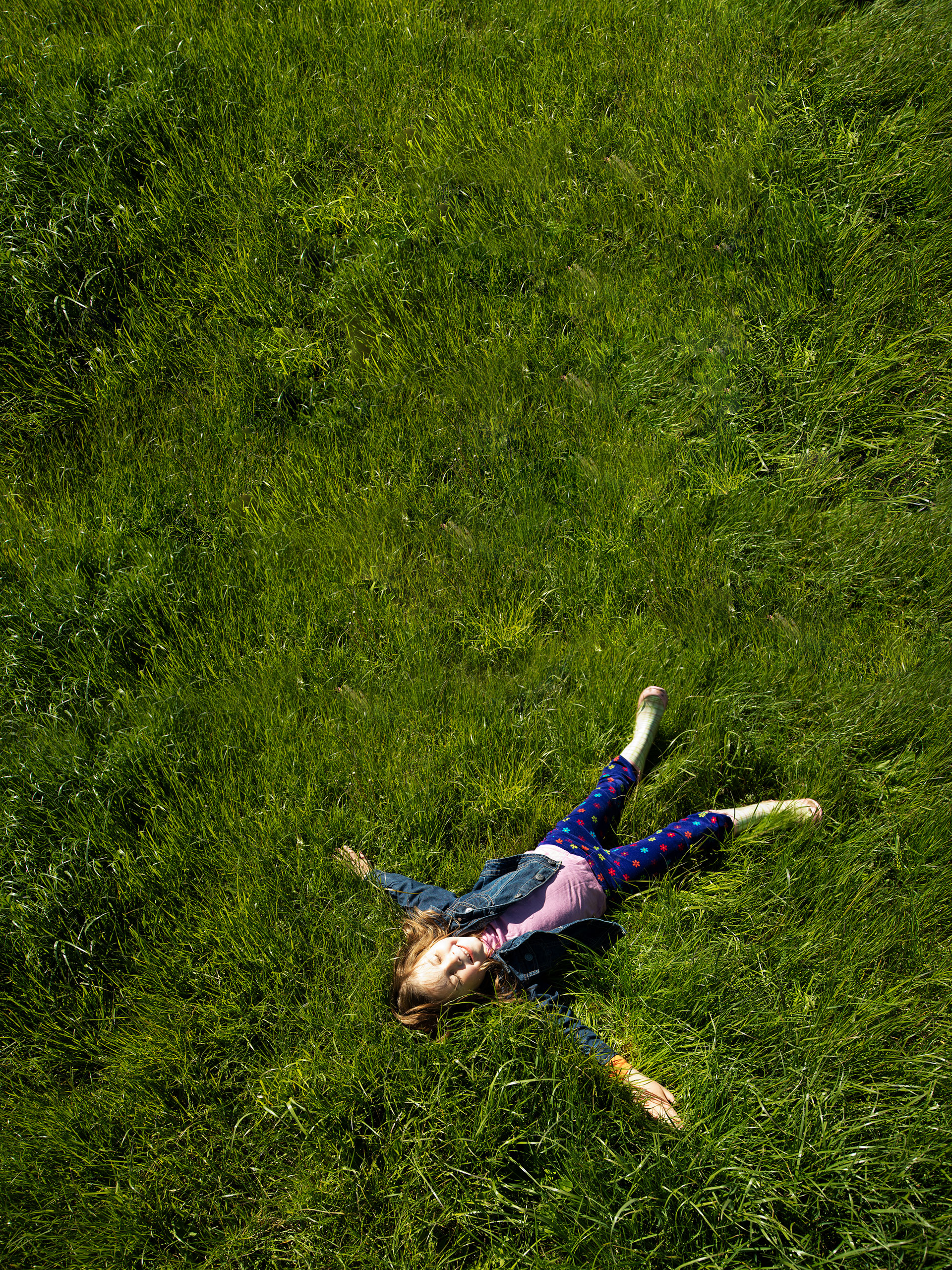 Happy Girl laying Down on Grass